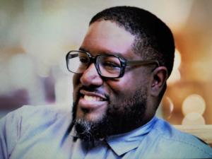 Headshot of Malik Singleton shows me smiling and wearing eyeglasses.