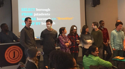 Photo of grad students standing before projection screen, participating in fun, human query result exercise.
